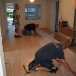 volunteers laying flooring inside a preservation and repair project