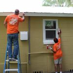 Home Depot volunteers painting exterior of house