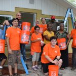 Group photo with Home Depot volunteers, homeowner, family, and Habitat staff