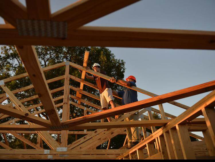Kaleb Ward, left, a senior at The Villages High School, and Bruce Haberle, construction management academy instructor, work on the roof trusses on a Habitat for Humanity home under construction Thursday at Winners Circle in Lady Lake. -Bill Mitchell, Daily Sun