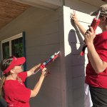 Wells Fargo volunteers caulking exterior