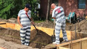 Chad Johnson, left, and Jared Hainey, inmates at the Lake County Jail, dig ditches that will be used to install plumbing for a home under construction by Habitat for Humanity of Lake-Sumter. (Martin E. Comas/Orlando Sentinel)