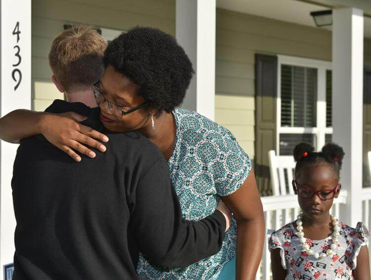 Swayde Farring, left, a senior at The Villages High School, hugs Jasmine Jacobs, center, of Lady Lake, as her daughter, Carmen, 6, stands by during the dedication of their new home Friday in Lady Lake. It's the first home VHS students have built through the school's construction management academy. -Bill Mitchell, Daily Sun
