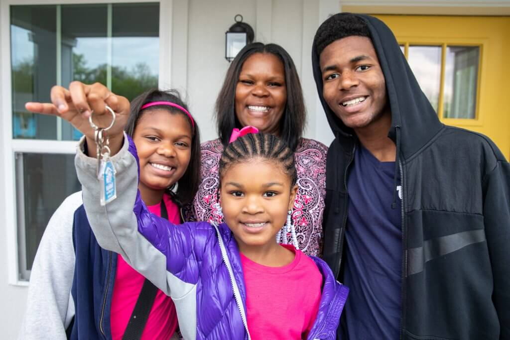smiling family holding key to new home