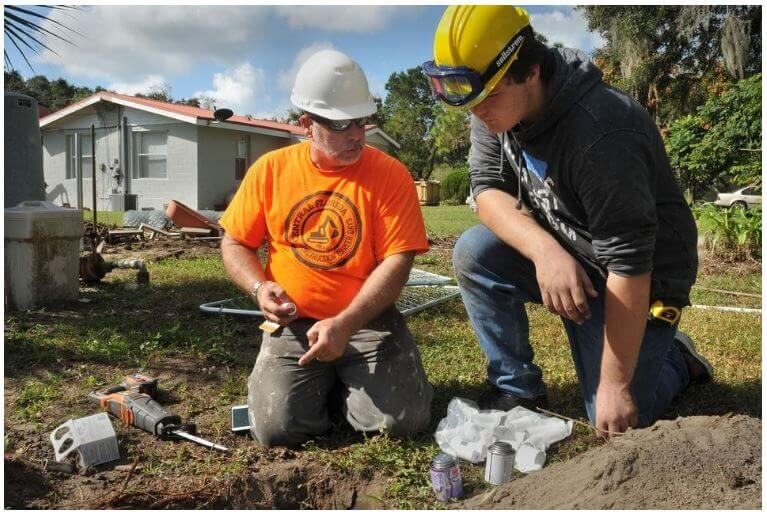 Instructor Dan McCauley helps Leesburg High School Construction Academy student Austin Marshall with plumbing on a project in 2018. [Daily Commercial file]
