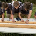 youth construction academy students signing 2x4 board