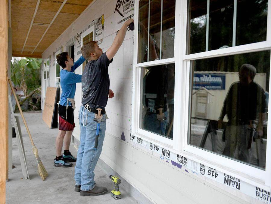 Under the direction of instructor Bruce Haberle, reflected right, The Villages High School Construction Management Academy seniors David Routzahn, 17, and Trey Jones, 19, make chalk lines for the siding on a Habitat for Humanity house Tuesday in Lady Lake. Photos by Cindy Skop, Daily Sun