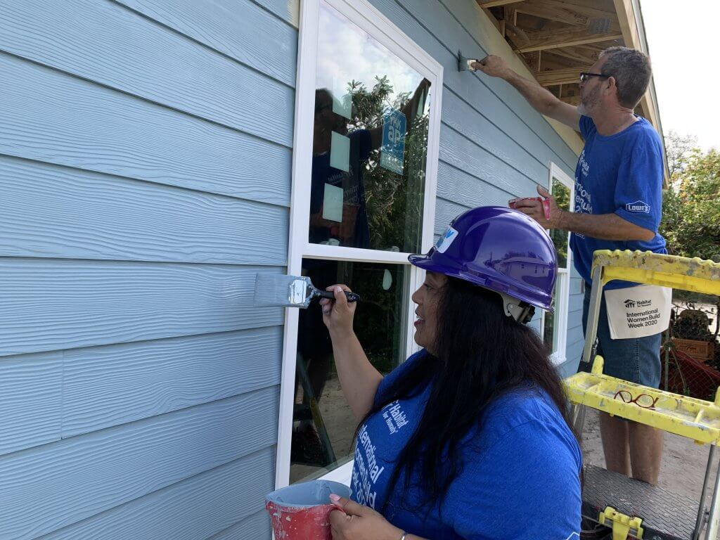 Habitat Lake-Sumter Homeowners Lorie and James painting the exterior of the home blue