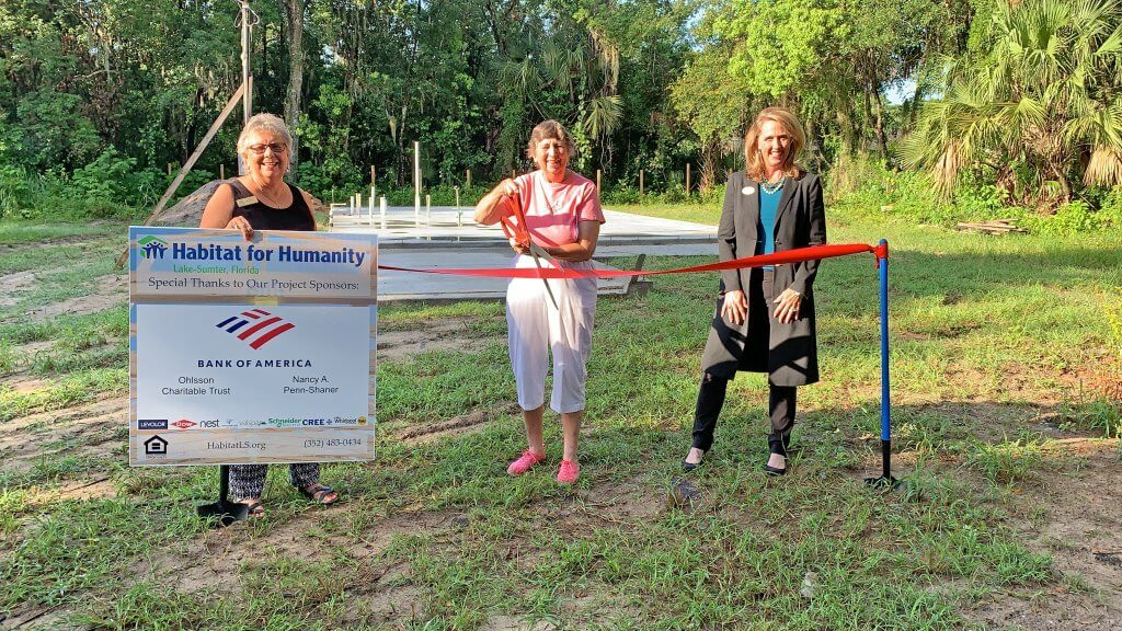 Mount Dora Mayor Catherine T. Hoechst, Nadine Foley, and Monica Wofford pose for a ribbon-cutting ceremony on July 7 for a new home to be built by Habitat for Humanity of Lake-Sumter.