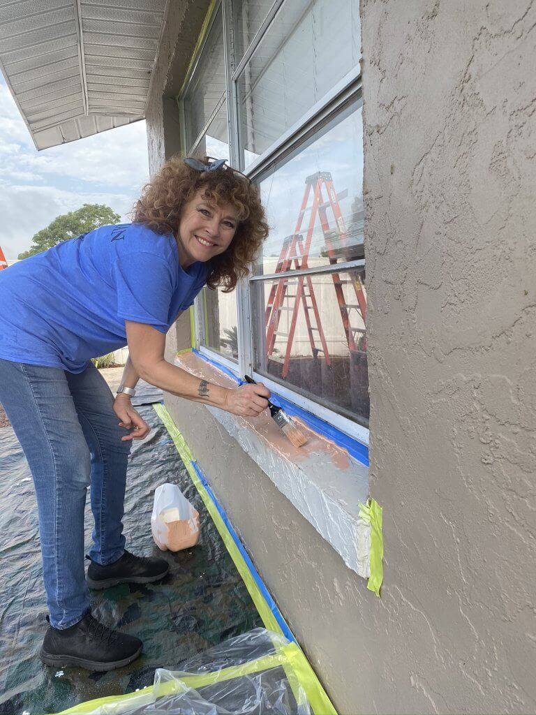 Diane Treadway, president of Leesburg Evening Rotary Club, does exterior painting on a Leesburg home as part of Habitat for Humanity's Preservation and Repair Program.