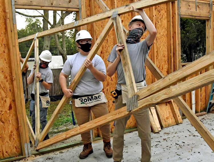 Joshua Fulwider, left, Abigail Stewart, center, and Jakobe Zick bring in a roof truss to be raised on a home being built for Habitat for Humanity Lake Sumter on Oct. 12 on Ann Street in Lady Lake.  George Horsford, Daily Sun