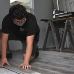 Leesburg High School Youth Construction Academy student working on flooring
