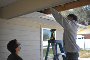 Leesburg High School Youth Construction Academy students working on soffit and fascia