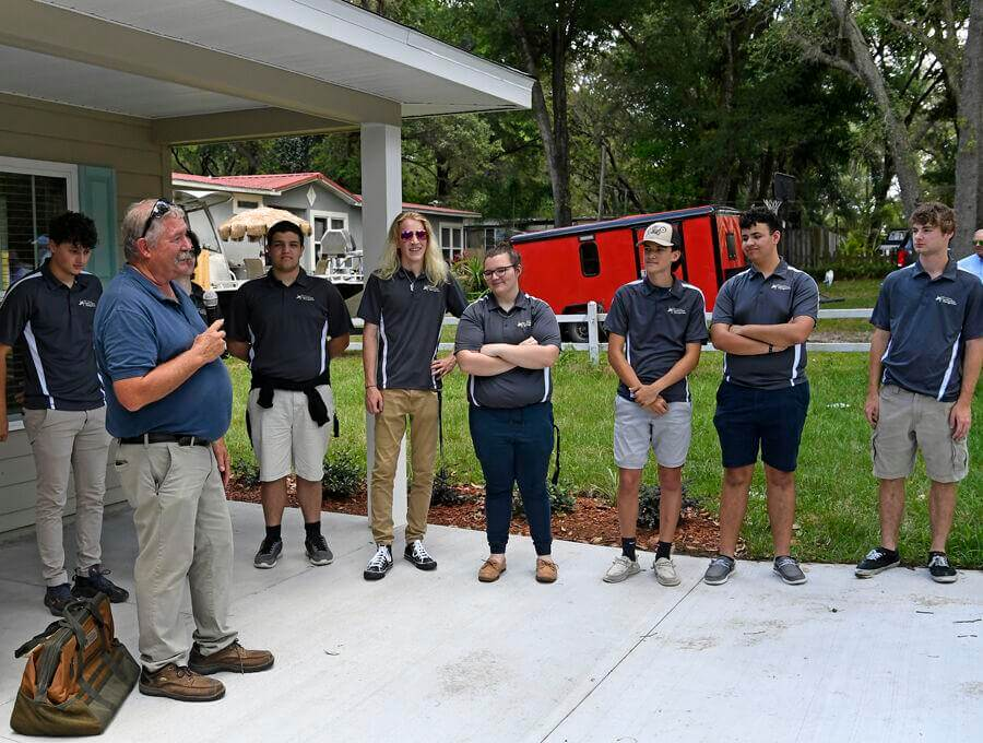 Instructor Bruce Haberle congratulates students with The Villages High School's Construction Management Academy for helping build a new home in Lady Lake for Amanda Brooks and her daughter, Emilee Carter.