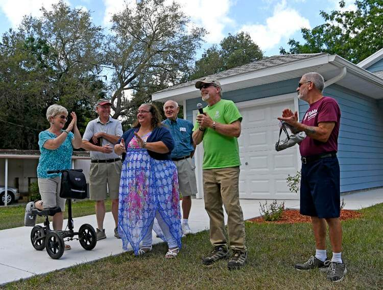 Members of The Villages Habitat for Humanity Club surround Joyce Tohill before she is given the keys to her new home in Fruitland Park. Tohill and her family will move in next month.